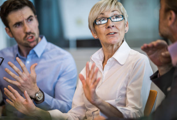 Please stop arguing! Senior businesswoman telling her colleagues to stop arguing on a meeting. conflict stock pictures, royalty-free photos & images