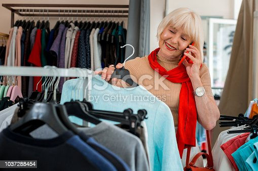 istock Pleased adorable elderly woman having a talk via mobile phone during shopping 1037288454