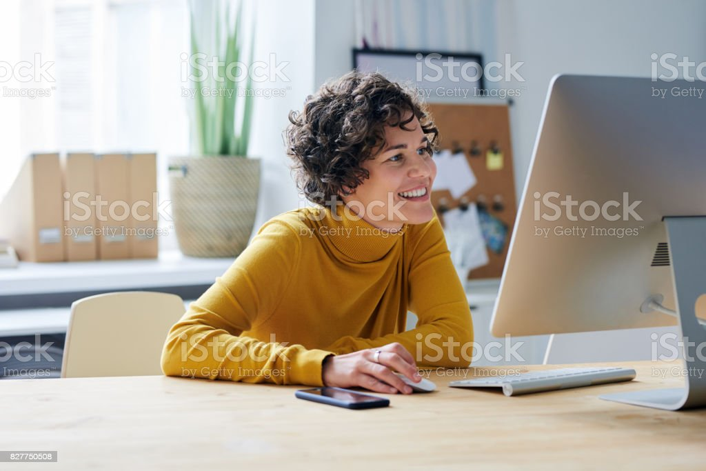 Pleased business lady in front of computer stock photo