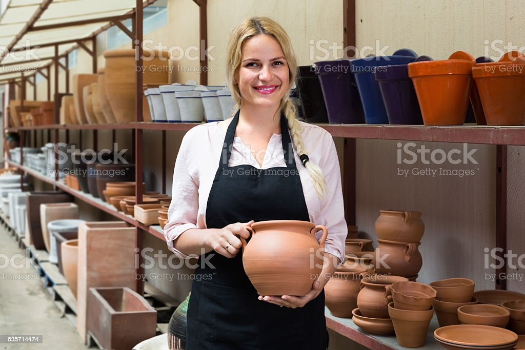 pleased female artisan having ceramics in workshop royalty-free stock photo