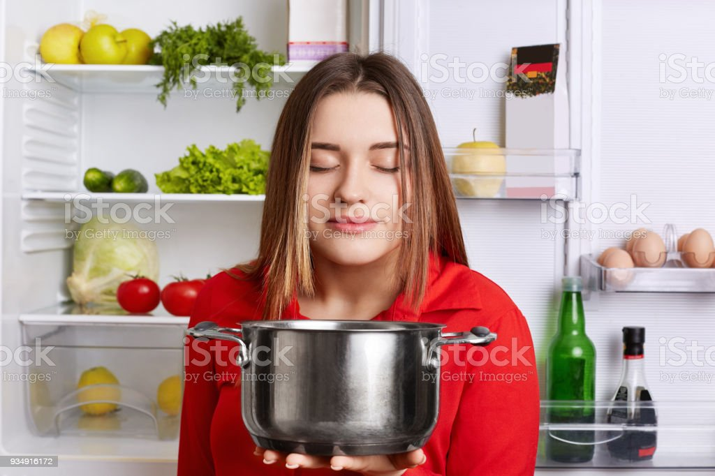 Pleased female holds saucepan, smells pleasant oudour, cooked delicious soup with vegetables, stands at kitchen near opened fridge. Female vegeterian satisfied with new recipe of dish. Cooking concept stock photo