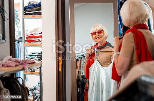 istock Pleased grey haired woman keeping summer dress in front of her in fitting room of shopping store 1037288008