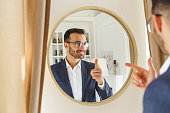 Waist-up portrait of a handsome stylish young Caucasian man looking at himself in the mirror