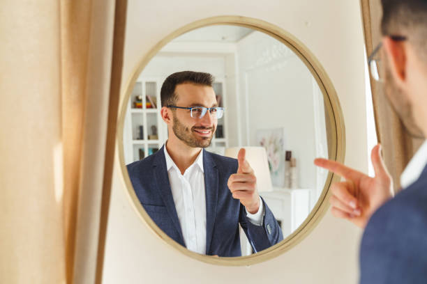 Pleased male wearing stylish suit and eyeglasses stock photo