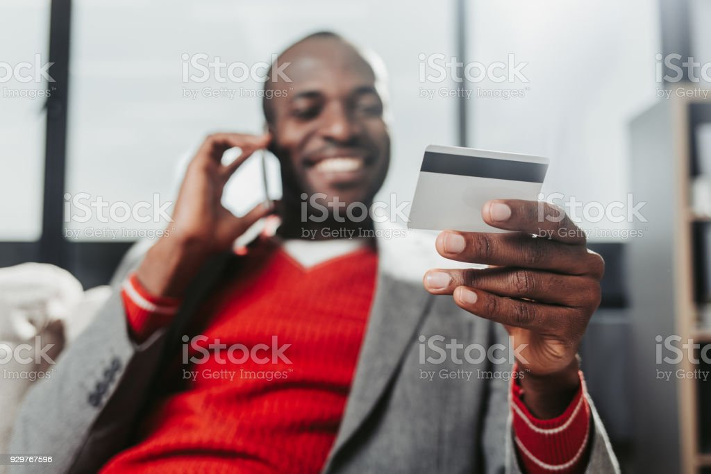Pleased male with bankcard talking by smartphone stock photo