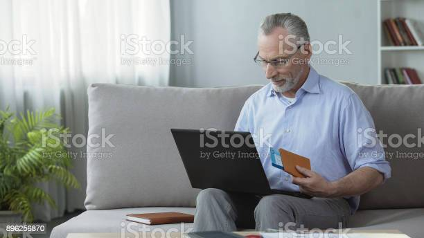 Pleased old male booking hotel room on laptop holding passport and picture id896256870?b=1&k=6&m=896256870&s=612x612&h=n2nynww8swczsgrrg 1wdm4njqmhpfcccimi yuhhw4=