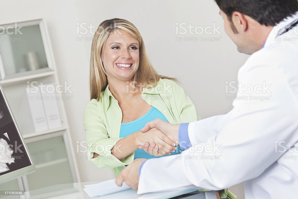 Pleased pregnant woman shaking her doctor's hand after sonogram visit royalty-free stock photo