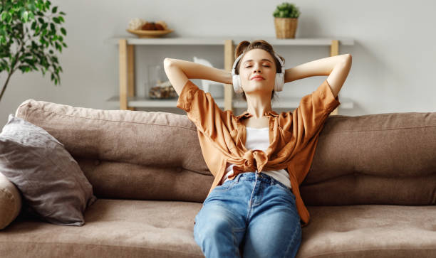 pleased young woman in headphones listening to music while relaxing on sofa at home - mani dietro la testa foto e immagini stock