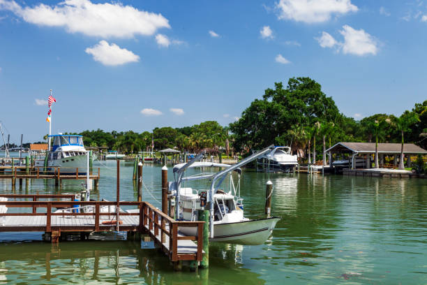 Pleasure Boats and Fishing Boats, most with Flags flying - all moored to personal docks at a tree lined inland water way - it's a Tampa Bay Florida Lifestyle that aways includes the Water