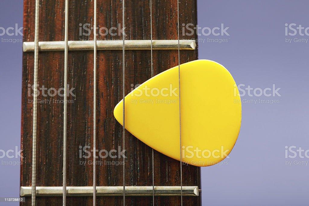 Plectrum between strings stock photo