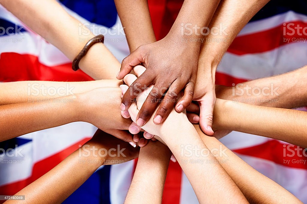 Pledging allegiance to the British flag: many hands stacked up stock photo