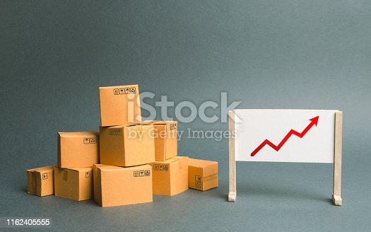 1155852718istockphoto Plenty of cardboard boxes and whiteboard with red positive trend chart. Increasing consumer demand. rate growth of production of goods and products, increasing economic indicators. Trade balance 1162405555