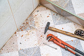 Plier, small hammer and neil on the restroom ground, with the dust from reparing in for broken pipe.