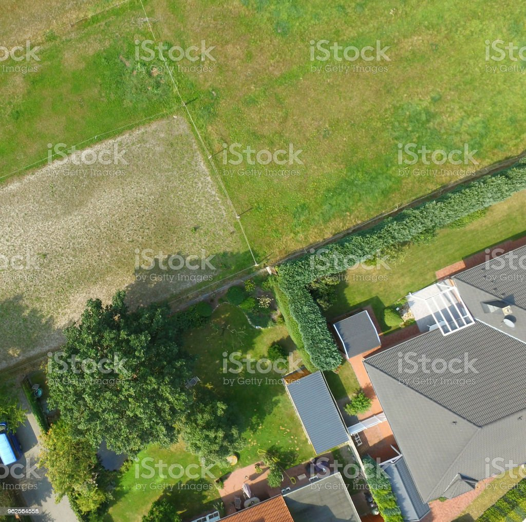 Plots with a meadow, a lawn, a detached house and a terraced house adjoin at one point, plot boundaries look like an abstract cross. - foto stock