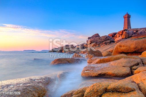 Ploumanach lighthouse or Phare de Men Ruz at the pink granite coast in Brittany, France during a beautiful summer sunset.