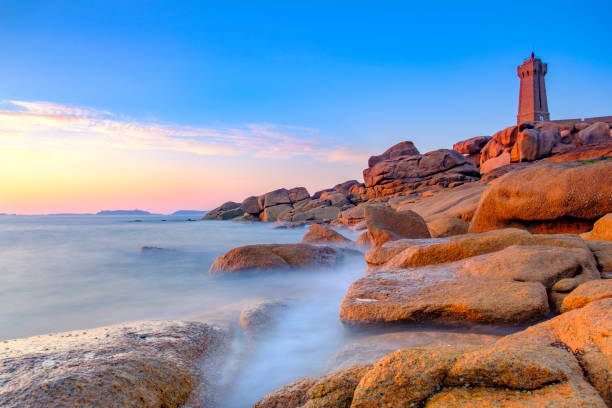 ploumanach lighthouse at the pink granite coast in brittany, france during sunset - rocky coastline stock pictures, royalty-free photos & images