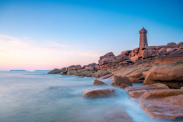 Ploumanach lighthouse at the pink granite coast in Brittany, France during sunset