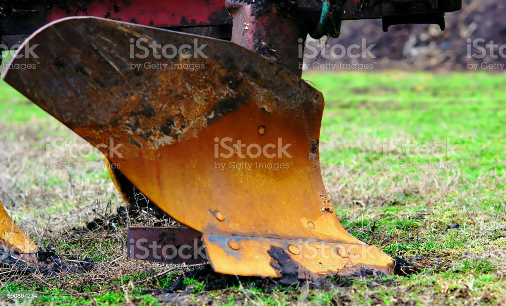 plow for plowing the land close up. Standing on the green grass of the field before preparing for the sowing process stock photo