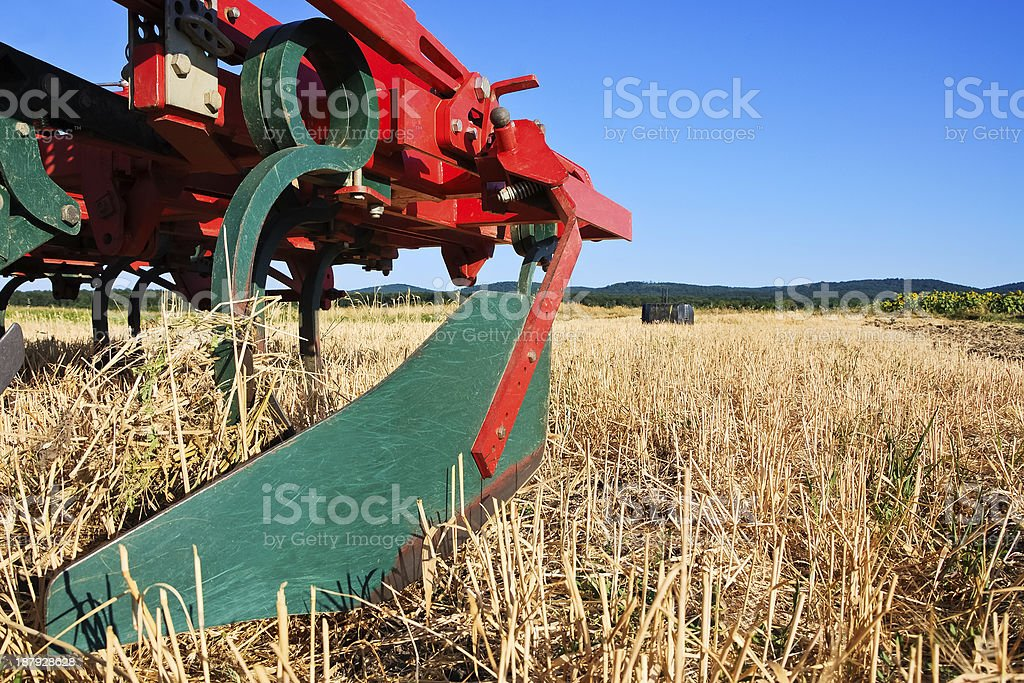 plow on a stubble field of wheat stock photo