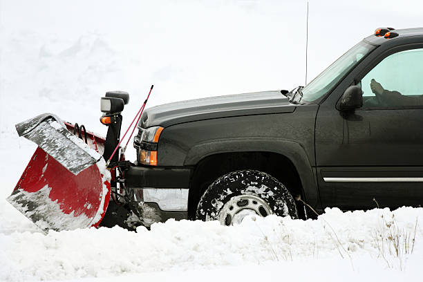 plow  removing snow on cold stormy day stock photo