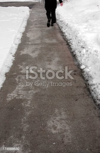 Unrecognizable person walking on plowed and salted sidewalk in Toronto