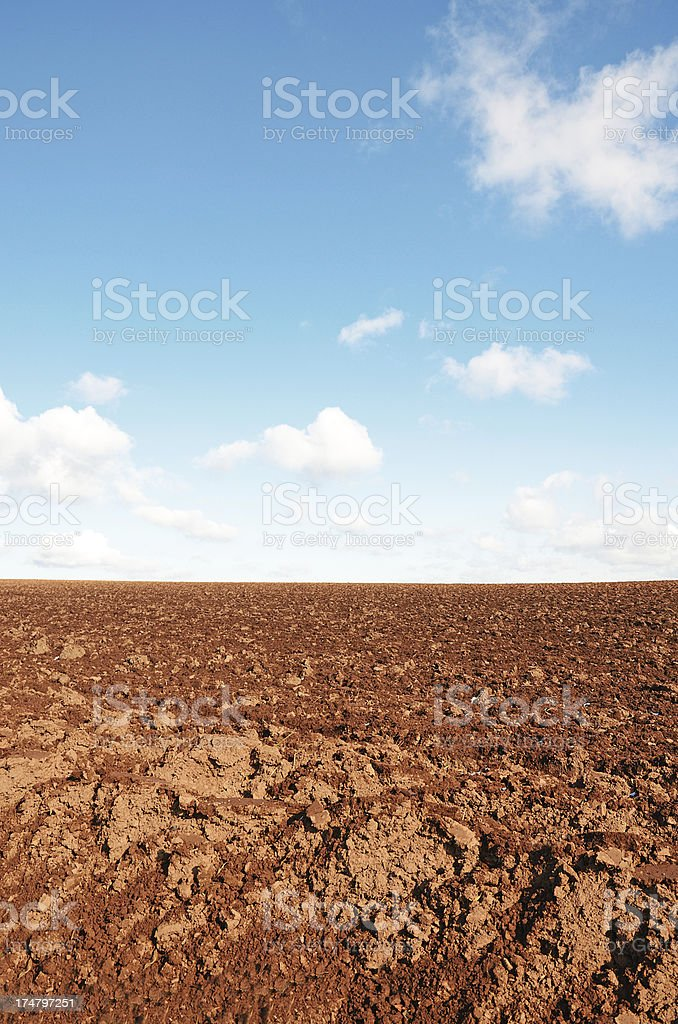 Plowed red soil under clear blue sky in autumn royalty-free stock photo