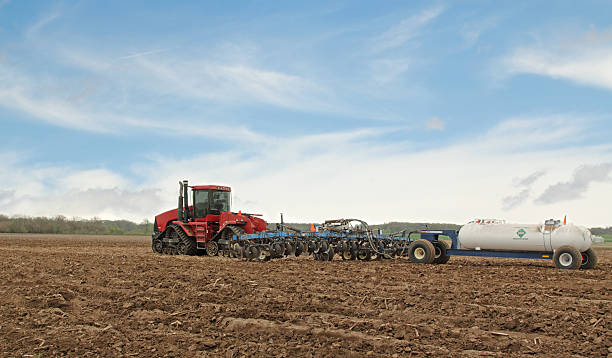 Plowing a Farm Field Red tractor pulling plow and anhydrous ammonia tank anhydrous stock pictures, royalty-free photos & images