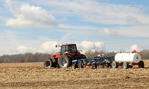 Plowing and Fertilizing Farm Field Red tractor pulling plow and anhydrous ammonia tank anhydrous stock pictures, royalty-free photos & images