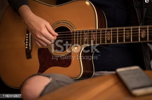 Close up shot of a young woman playing a guitar in a cafe