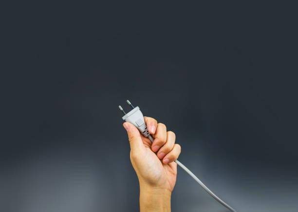 Plug hand holding on black background stock photo