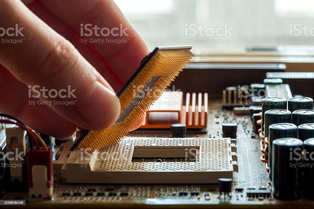 plug in CPU microprocessor to motherboard. stock photo