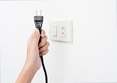 Plug on hand or unplug and outlet on white wall background , electric shock