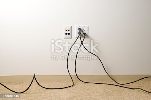 Electrical extensions chords plugged into wall in an office space.