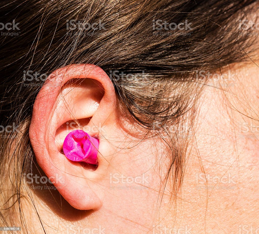 Plugged womans ear stock photo