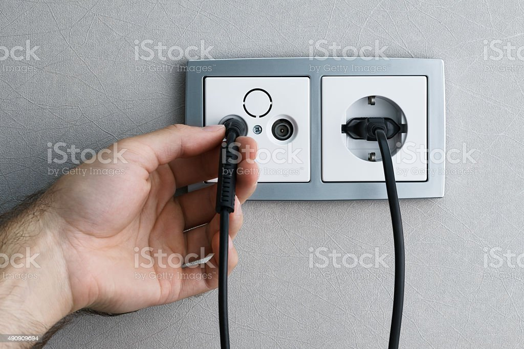 Plugging cable to outlet stock photo