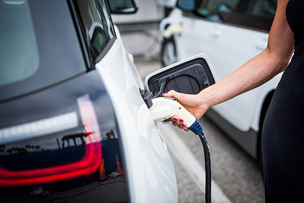 Plugging the power cord Unknown female plugging the power cord to the electric car socket to recharge its battery. battery charger stock pictures, royalty-free photos & images