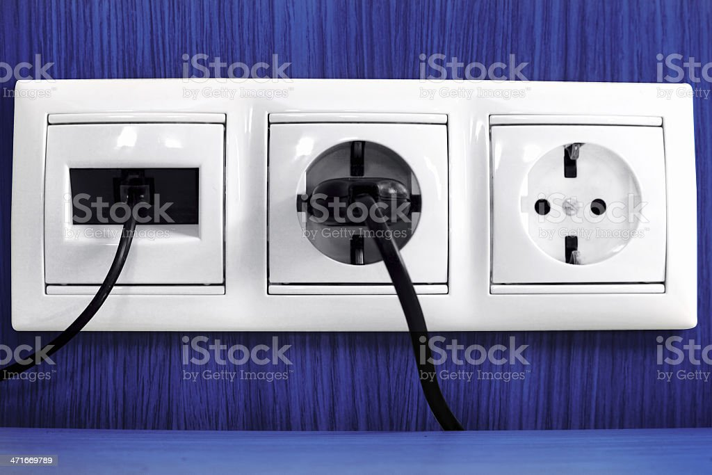 Plugs in electric and phone  socket. royalty-free stock photo