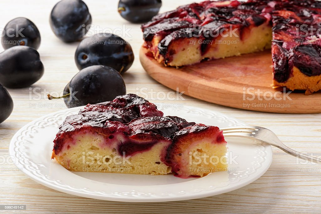 Plum bisquit cake on white wooden background. stock photo