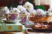 Plum cake, cups with green tea and flowers lying on a wooden table.