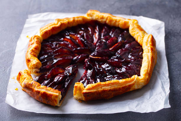 Plum galette, pie. Grey background. Close up. stock photo
