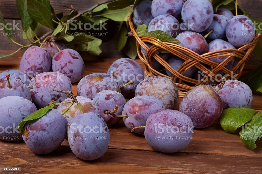 plum in a wicker basket on the wooden background stock photo