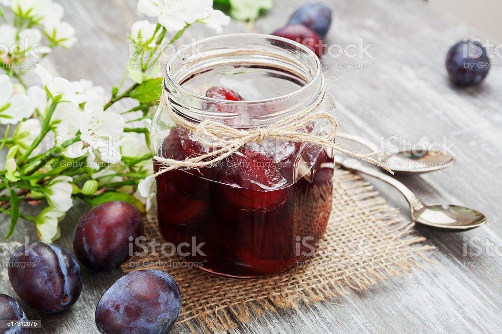 Plum jam in a glass jar stock photo