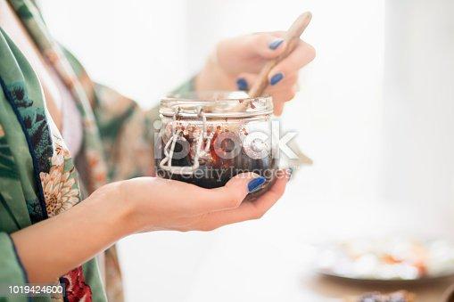 Close-up shot of a females hand holding jar of plum jam.