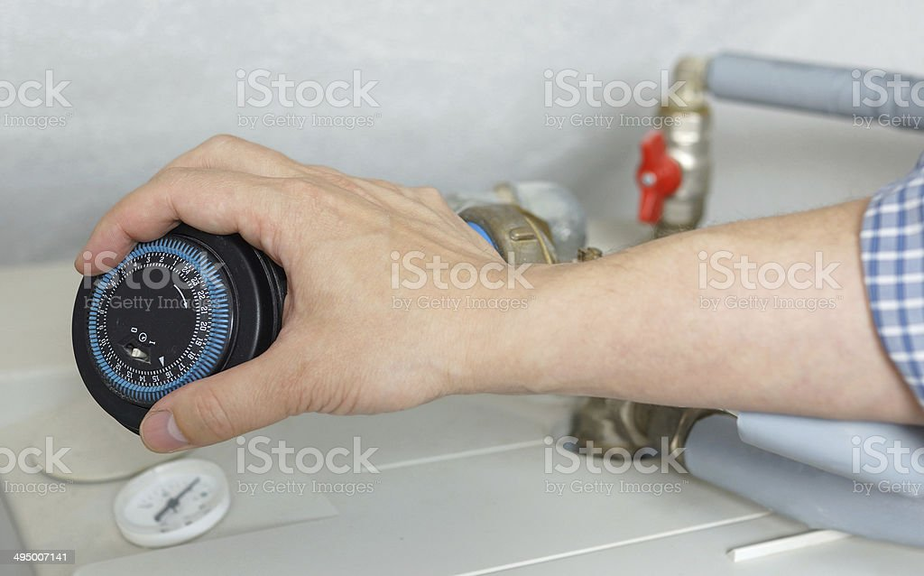 plumber adjusting the clock on the boiler stock photo