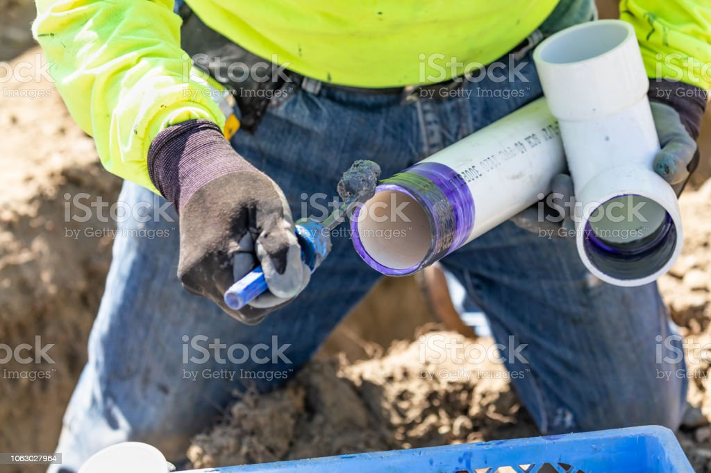 Plumber Applying Pipe Cleaner, Primer and Glue to PVC Pipe At Construction Site stock photo