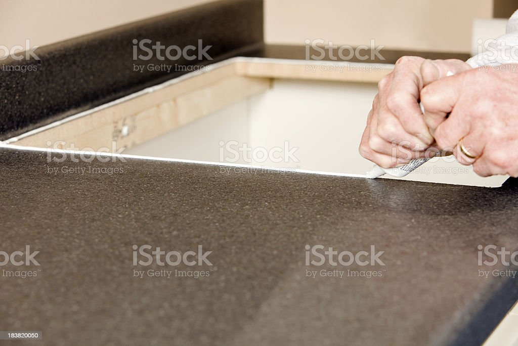 Plumber Applying Silicone Caulk to Countertop Sink Opening stock photo