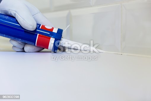 Plumber applying silicone sealant to the countertop and ceramic tile. Home improvement, kitchen renovation concept