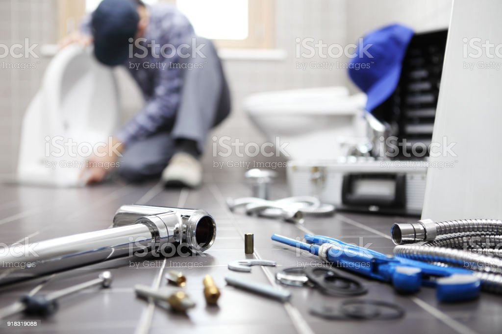 plumber at work in a bathroom, plumbing repair service, assemble and install concept stock photo