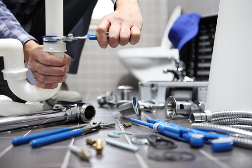 istock plumber at work in a bathroom, plumbing repair service, assemble and install concept 944254328