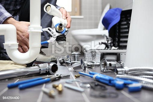 istock plumber at work in a bathroom, plumbing repair service, assemble and install concept 944254400